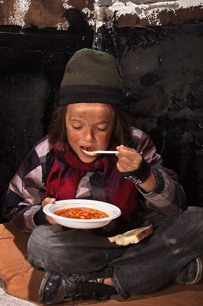 Poor beggar child eating charity food on