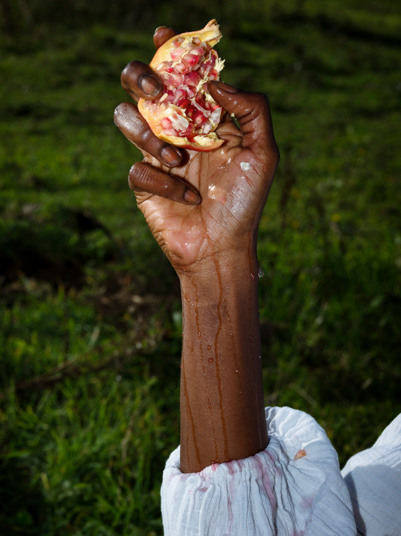 pomegranate held by black woman