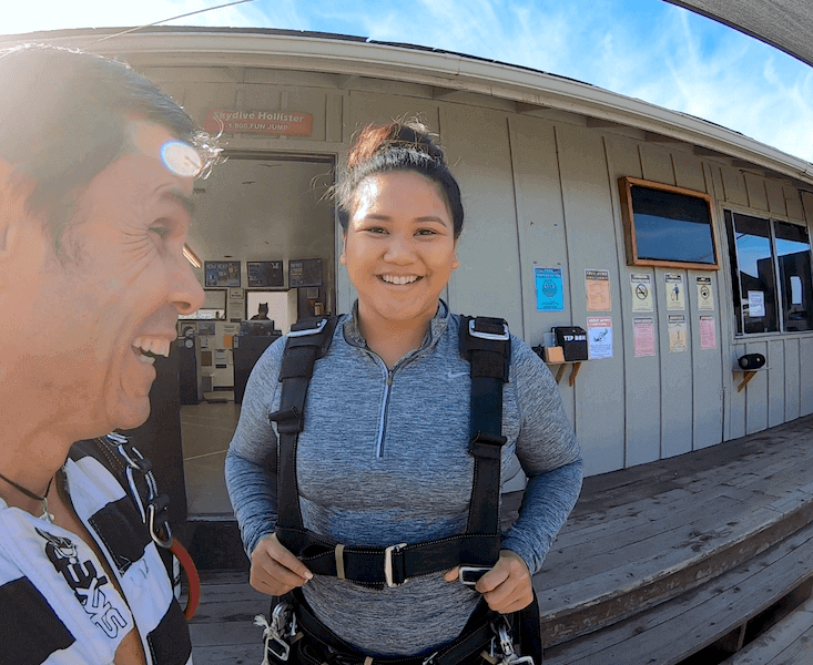 Jesica, a first time tandem student, with her instructor Lutchy in front of the Skydive Hollister office