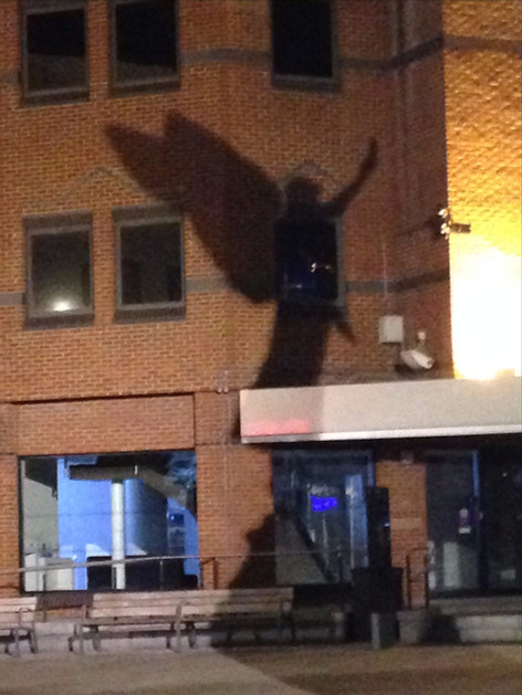 Woking's Town Centre angel in shadow on the wall of Barclay's Bank