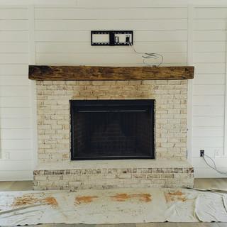 Hand Hewn Mantel On White Brick Fireplace