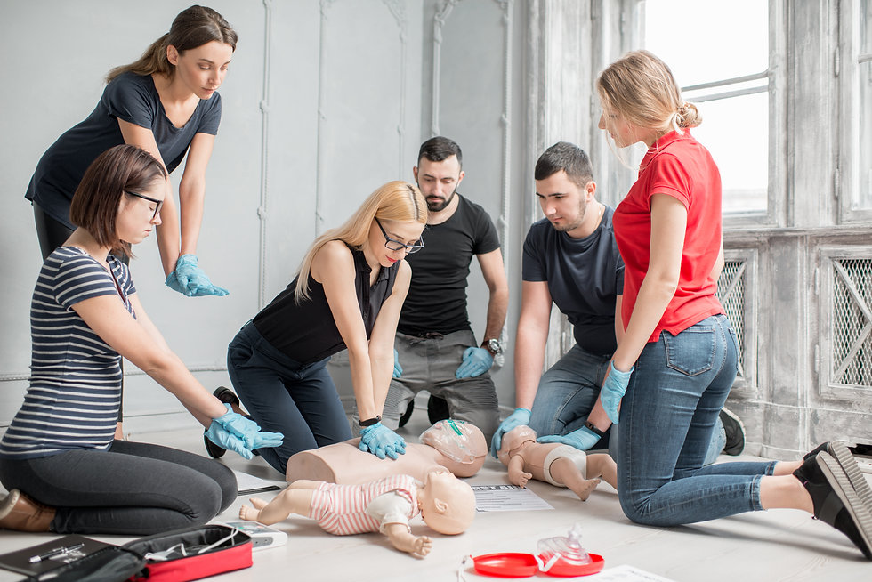 Group of people learning how to make first aid heart compressions with dummies during the