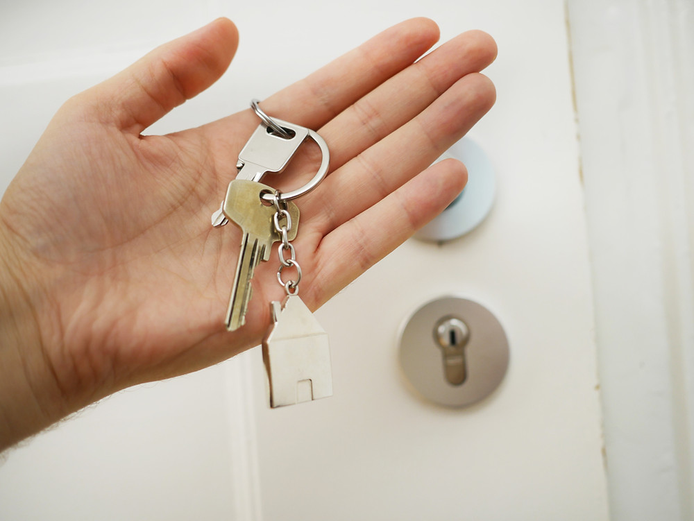 hand holding keys with house shaped keychain