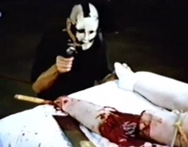 Masked man filming a woman leg being sawn of in American Guinea Pig Bouquet of  Guts and Gore horror film