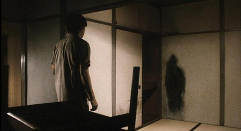 scene from film Kairo with scary mark on the wall