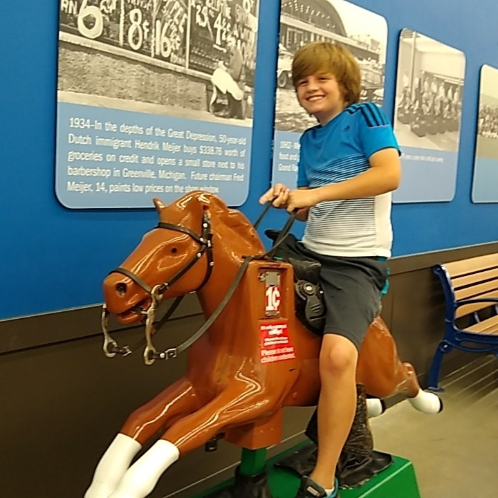 Eli completing a GooseChase mission by riding Sandy the Horse at Meijer.