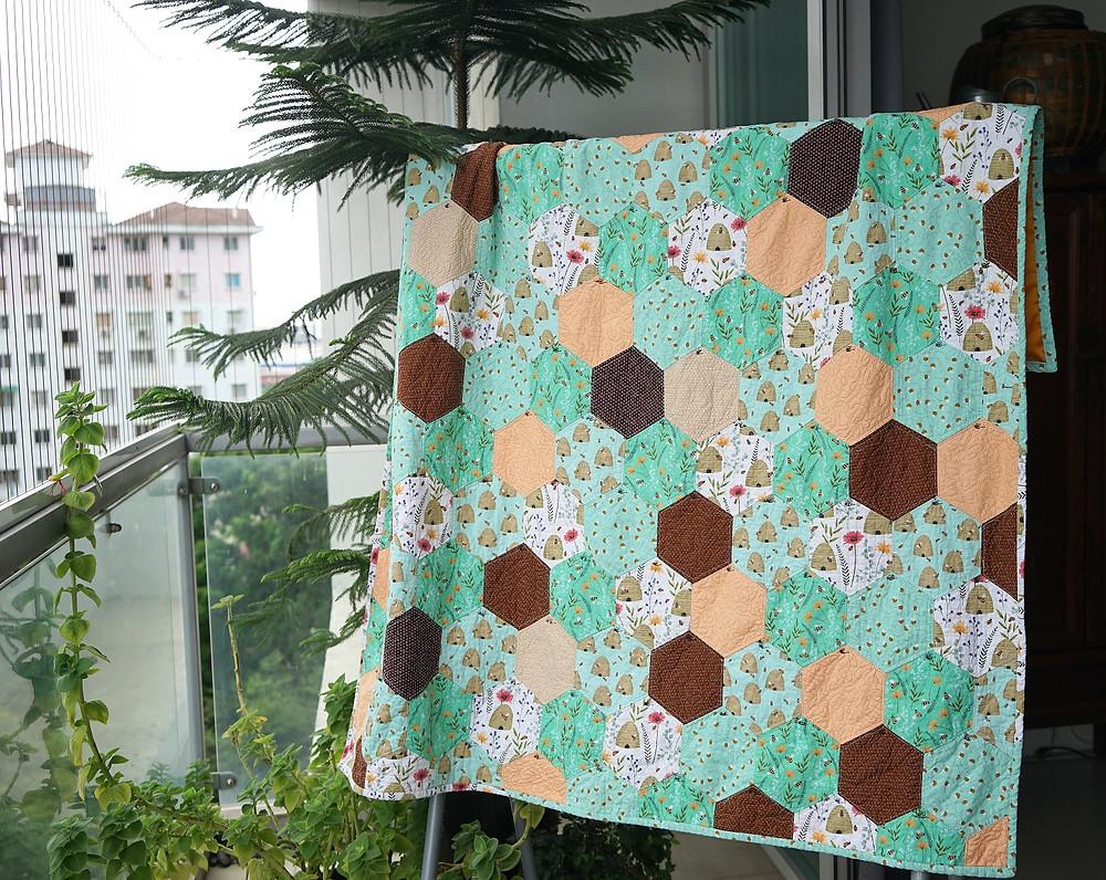 Honeycomb hexagon quilt hanging on display QAYG machine sewn