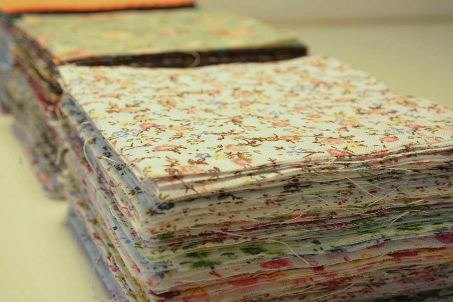 Stacks of pre-cut fabric squares.