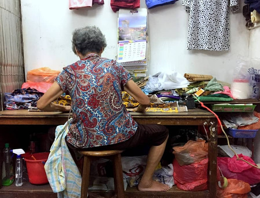 An old seamstress preparing the fabric for her next project.