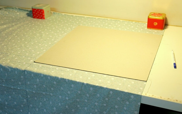 Place cardboard onto fabric and trace lines.