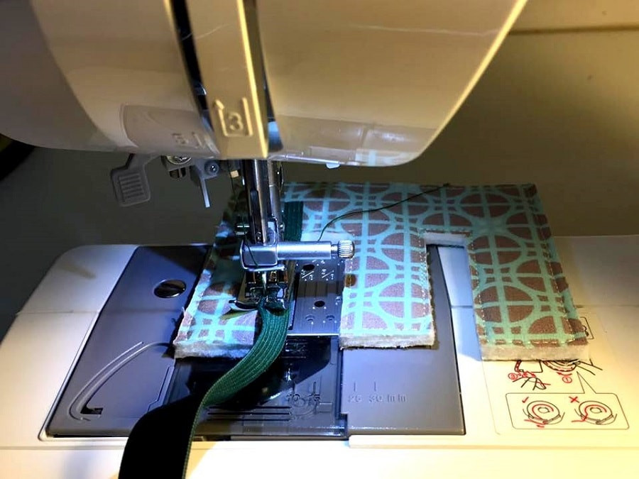 Sewing binding on Letter E using sewing machine.