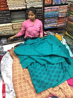 Lady measuring colourful ethnic fabric in a textile shop in Kolkata, India.