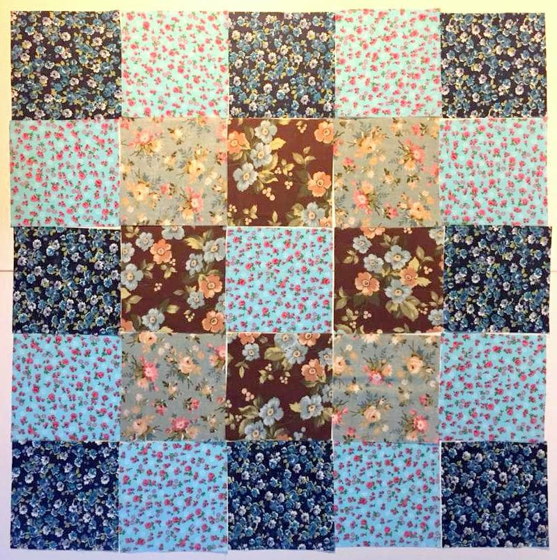 Turquoise-brown-grey fabric squares arranged for patchwork wall art.