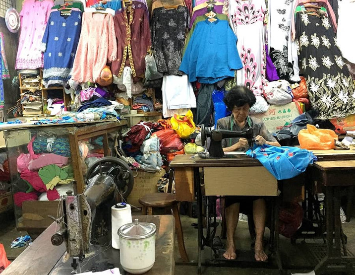 An old tailor working on a customer's order at Kee Ann Road, Malacca.