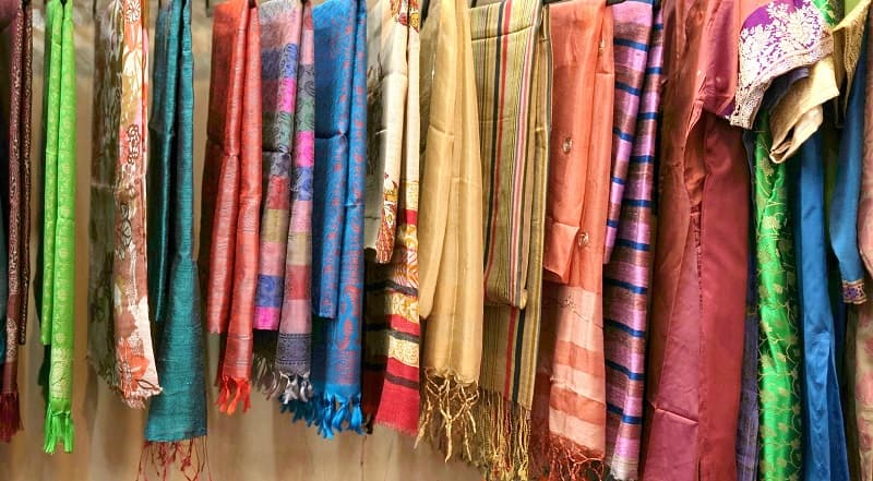 Colourful ethnic fabrics hanging on display in a textile shop in Varanasi, India.