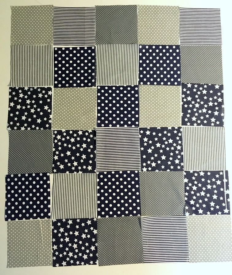 Dark Blue and grey themed fabric squares arrangement for patchwork.