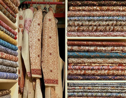 Colourful ethnic fabrics stacked in shelves in a textile shop in India
