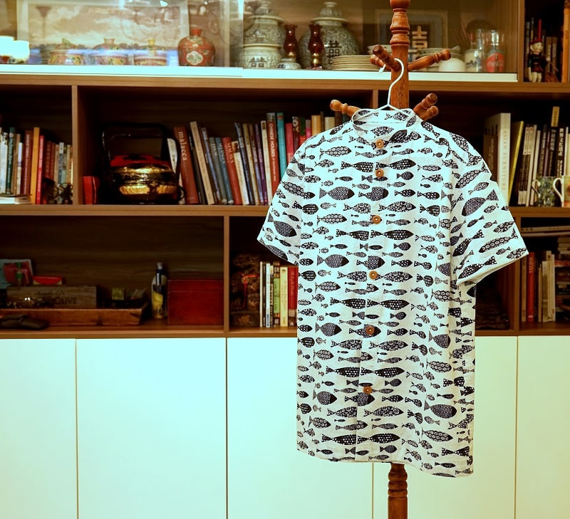 Men's button up shirt with mandarin collar, Japanese themed blue and white fish fabric. Hanging on a coat stand.