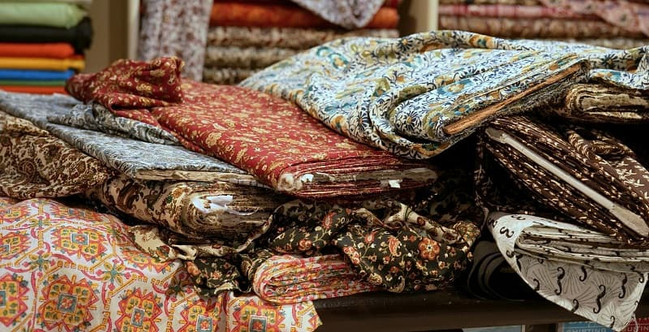Bolts of colourful ethnic fabrics in a textile shop in Jaipur, India.
