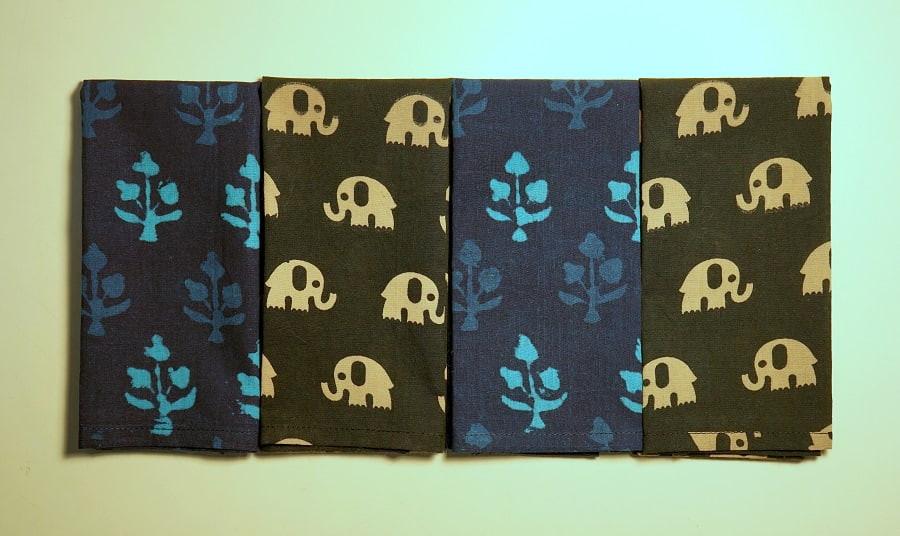 Indigo blue and black block print fabrics from India made into men's handkerchiefs, neatly folded.