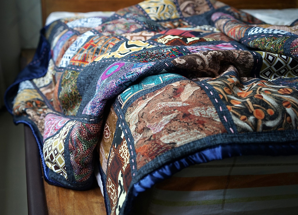 memory square patchwork quilt draped on bed close up