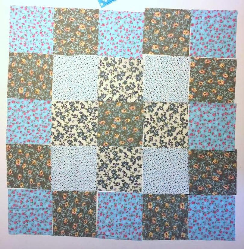 Turquoise-grey fabric squares arrangement for patchwork.