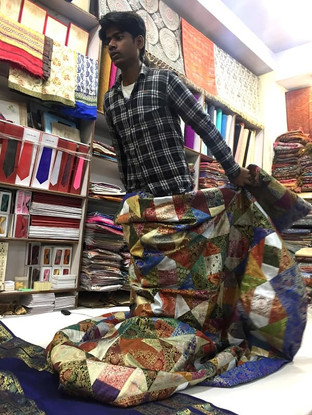 Main unfolding colourful ethnic fabric in a silk textile shop in Varanasi, India.