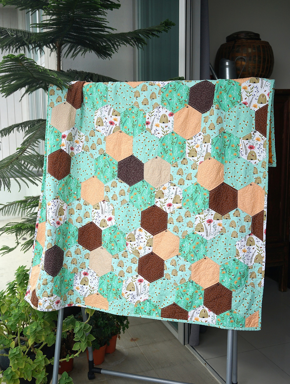 Honeycomb hexagon quilt hanging on display QAYG machine sewn green and brown