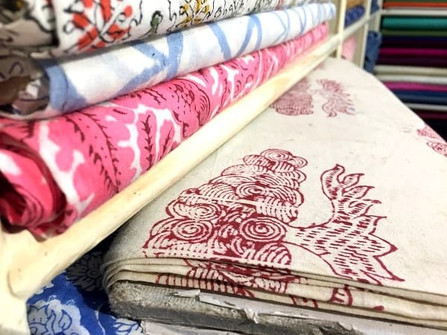 Blots of colourful ethnic fabrics on shelves in a textile shop in Jaipur, India