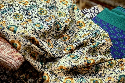 Ethnic floral fabric on bolts of other fabrics in a textile shop in Jaipur, India.