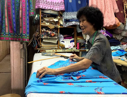 An old seamstress preparing the fabric for her customer's order.