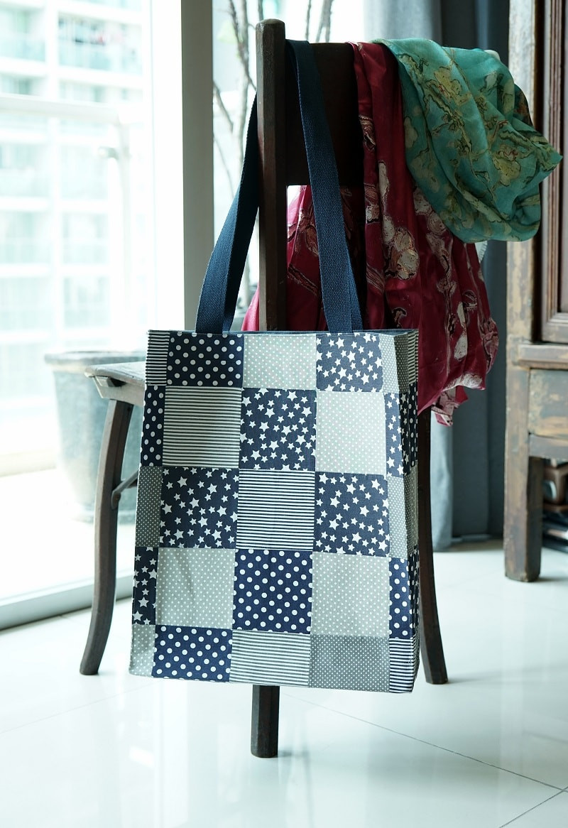 Blue grey patchwork tote bag hanging from a chair.
