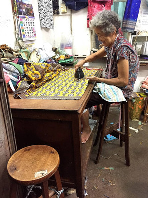 An old seamstress ironing the fabric for her next project.