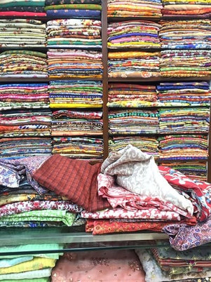 Colourful ethnic fabrics displayed on shelves in a textile shop in Kolkata, India