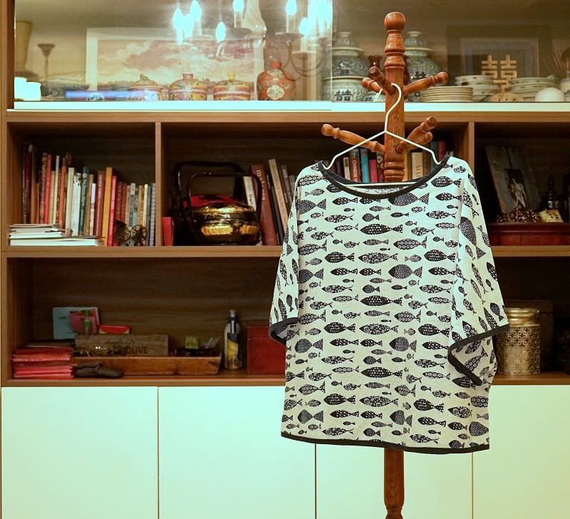Woman's blouse with kimono sleeves with Japanese blue and white fabric hanging on a coat stand.