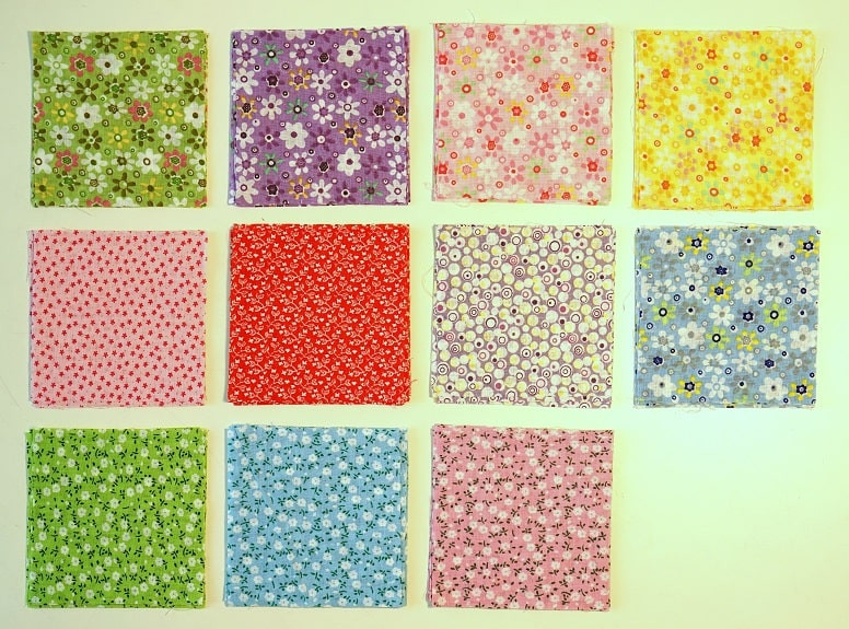 Fabric squares with small flowers on bright background arranged in grid.