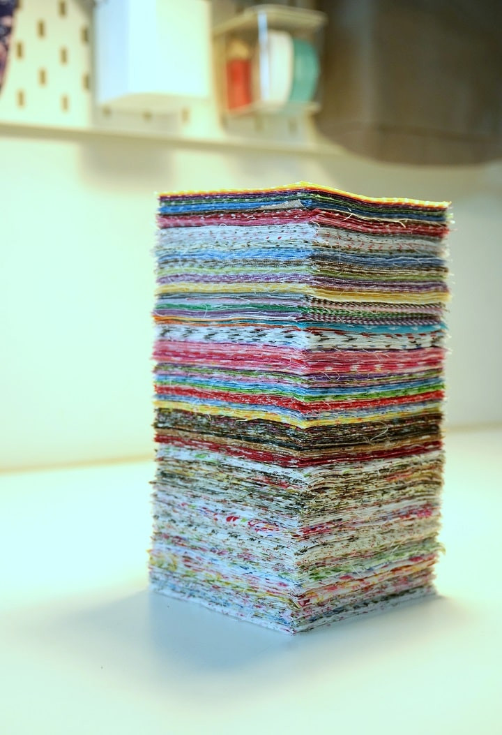 A tall stack of pre-cut fabric squares.