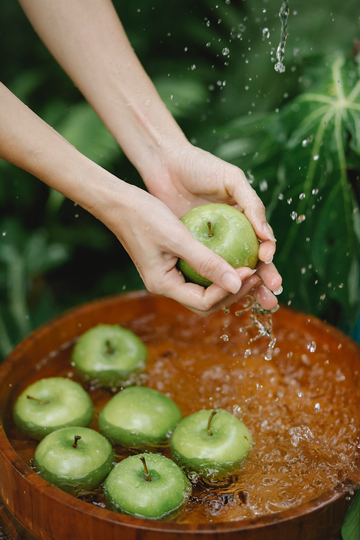 mains de femme lavant des pommes vertes