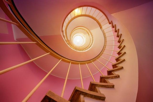 escalier en colimaçon doré et murs roses