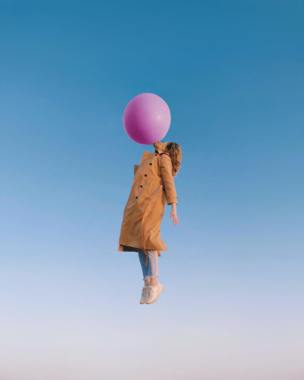 femme suspendue dans les airs accrochée par la bouche à un ballon