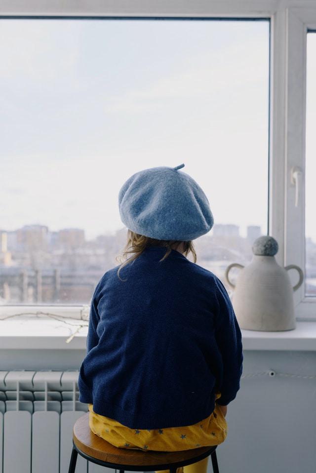 enfant assise de dos regardant par la fenêtre