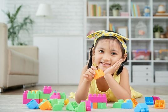 little-asian-girl-lying-floor-home-playi