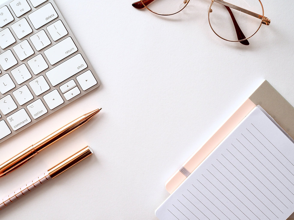 Imagem de uma mesa com teclado, óculos de grau, canetas e bloco de anotações em cima.