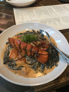 Lobster tail over squid ink linguine in a lobster cream sauce from Siena Tavern in Chicago.
