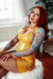 Denver Dominatrix Mistress Nicci is wearng yellow PVC dress wth her red hair