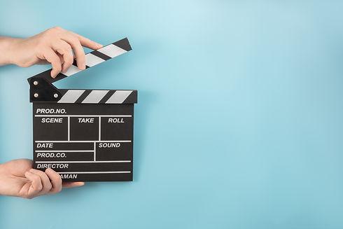 movie-clapperboard-hands-blue-space.jpg