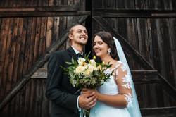 Mladomanželia pri drevenej stodole s kyticou v rukách