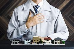 作業着の男性と模型の家
