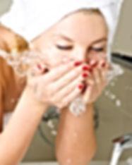 beautiful young woman washing her face i