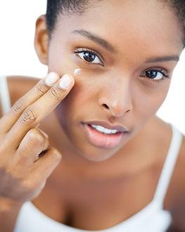 Pretty woman putting moisturizer on her